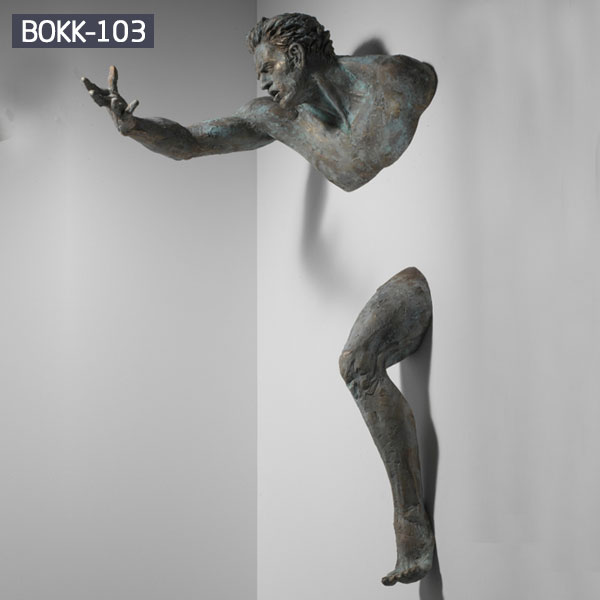 Bronze metal statue replica of matteo pugliese artists designs the man out of wall