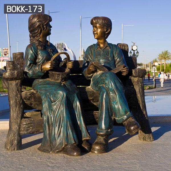 Outdoor park garden decor girl and boy sitting on the bench talking bronze sculpturesOutdoor park garden decor girl and boy sitting on the bench talking bronze sculptures