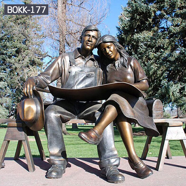 A couple is sitting on bench reading maps together metal outdoor sculptures