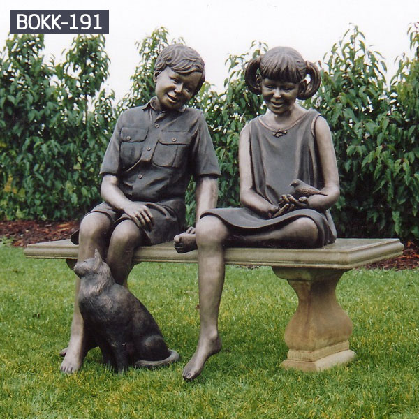 Boy and girl sitting on the bench talking with a cat bronze sculptures outdoor