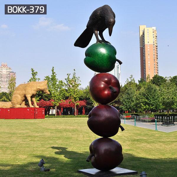 A bird standing at four apple bronze sculptures outdoor