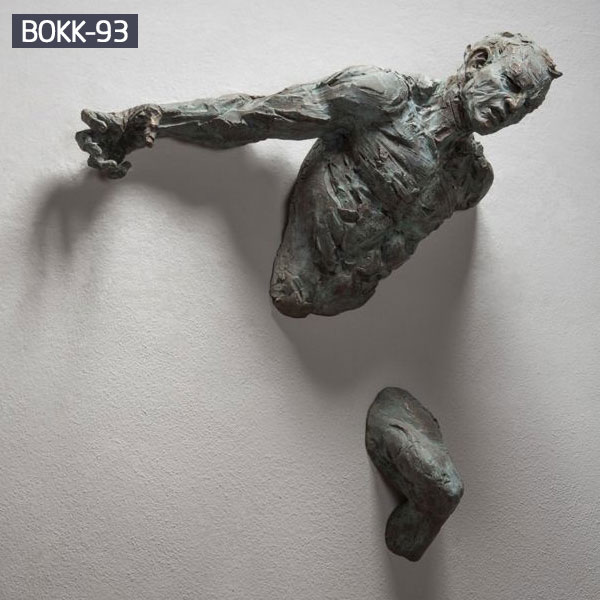 Bronze man coming out of wall sculpture for sale